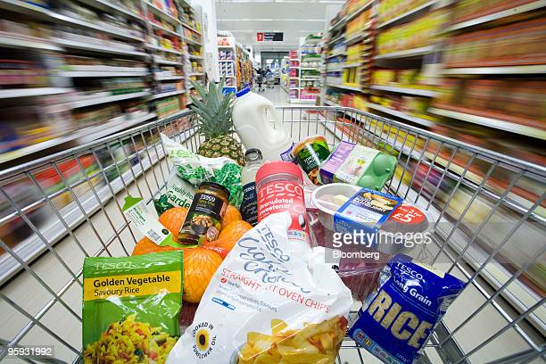 A shopping cart filled with items is pushed down the aisle at a Tesco supermarket in London UK on Tuesday Jan 19 2010 Tesco is freezing the VAT on...
