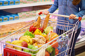 Woman pushing shopping cart with healthy food, when she walking over supermarket