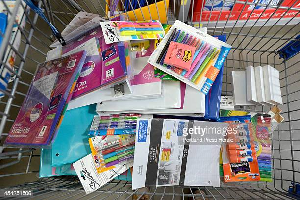 Shopping cart full of school supplies as parents and their children shop for school supplies at Walmart in Scarborough
