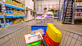 Shopping cart in Hardware store with brandless cement, tools and other goods to lay concrete floor