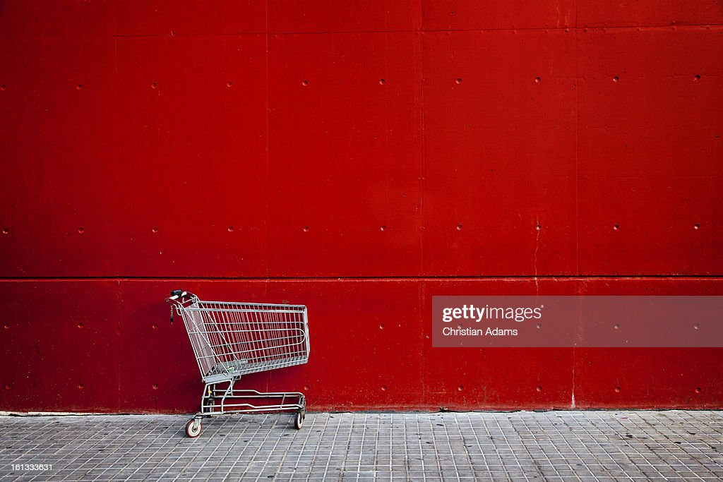 Shopping cart in front of a red wall