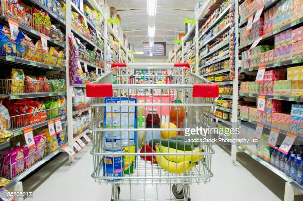 Shopping cart in grocery store aisle