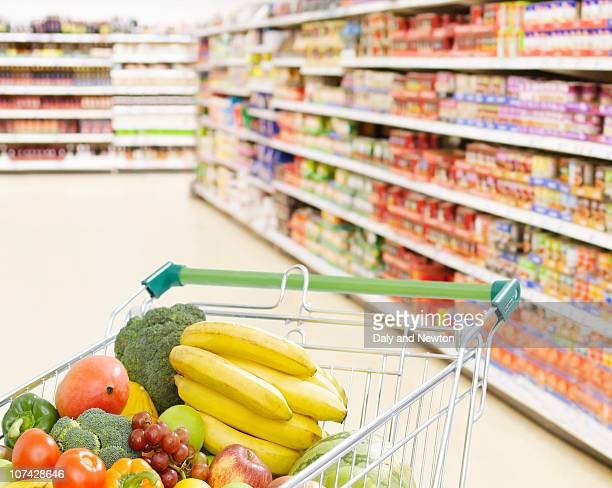 Shopping cart in grocery store full of fruits and vegetables