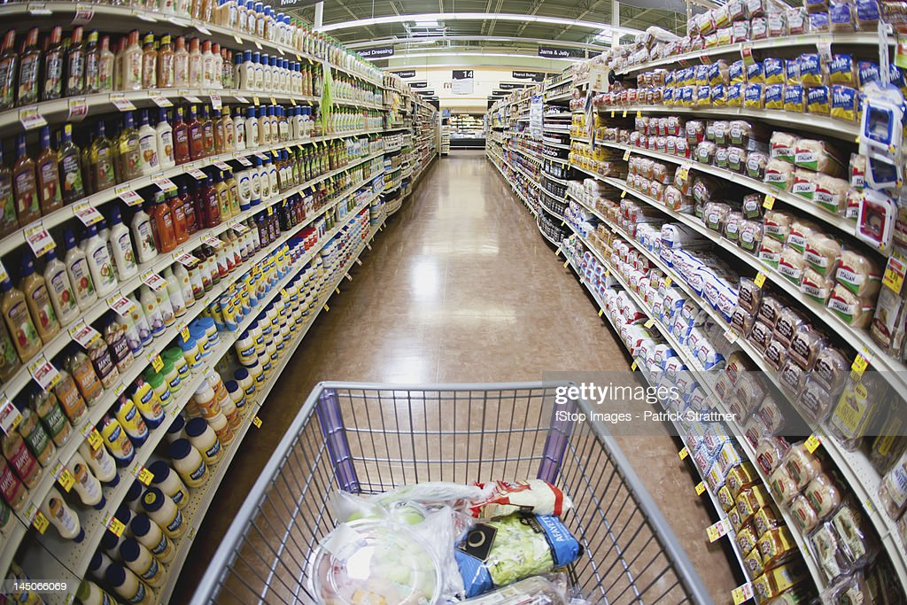 A shopping cart on an aisle in a supermarket, personal perspective : Stock Photo