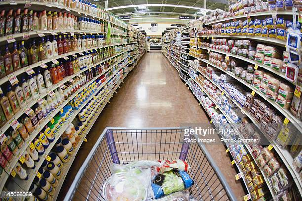 A shopping cart on an aisle in a supermarket, personal perspective