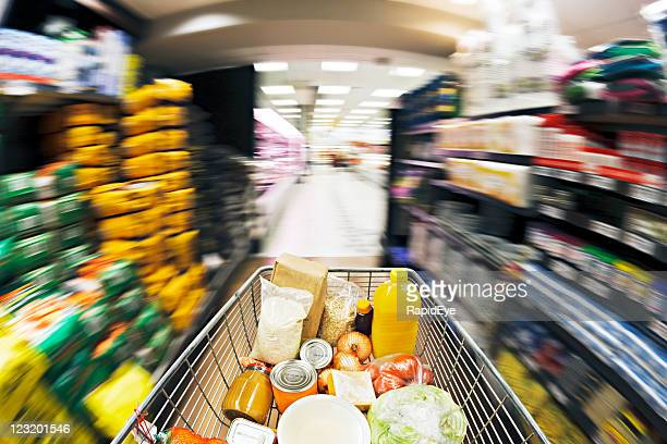 Shopping cart races down aisle. Fisheye lens and motion blur.