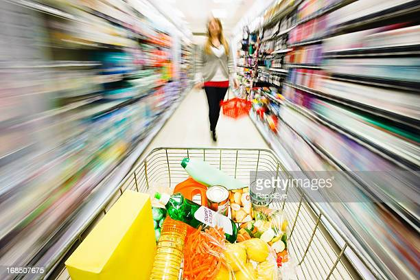 Shopping cart races past blurred shelves towards woman shopper