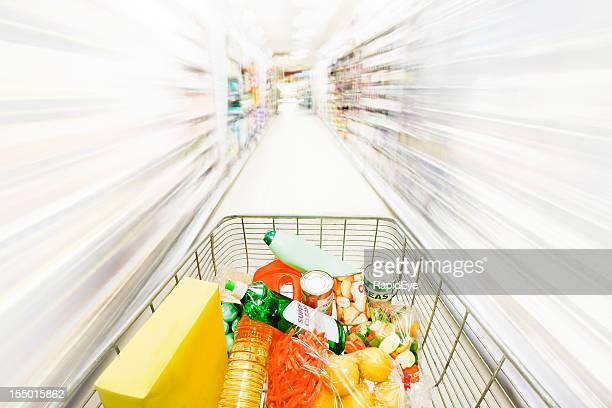 Shopping cart races through blurred, white shelves