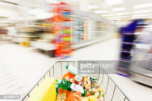 Shopping cart races towards supermarket aisle blurred by speed