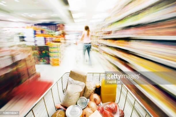 Shopping cart shows extreme motion blur racing through supermarket
