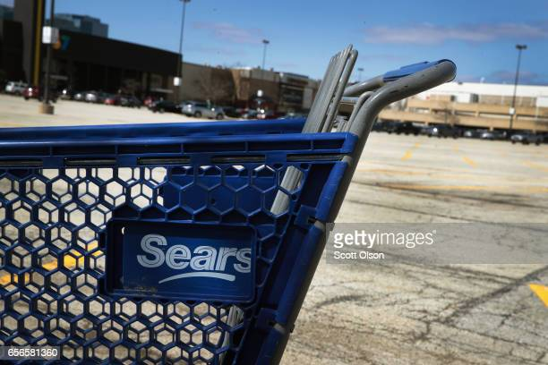 A shopping cart sits in the parking lot of a Sears retail store on March 22 2017 in Schaumburg Illinois Sears Holdings the parent of Kmart and Sears...