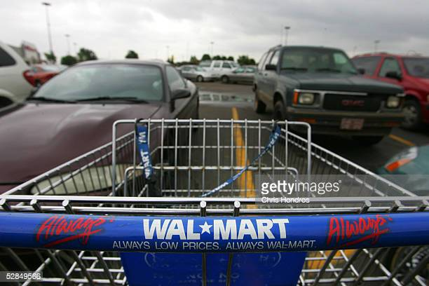 A shopping cart sits in the parking lot of a WalMart May 14 2005 in Oklahoma City Oklahoma WalMarts are now nearly ubiquitous on the American...