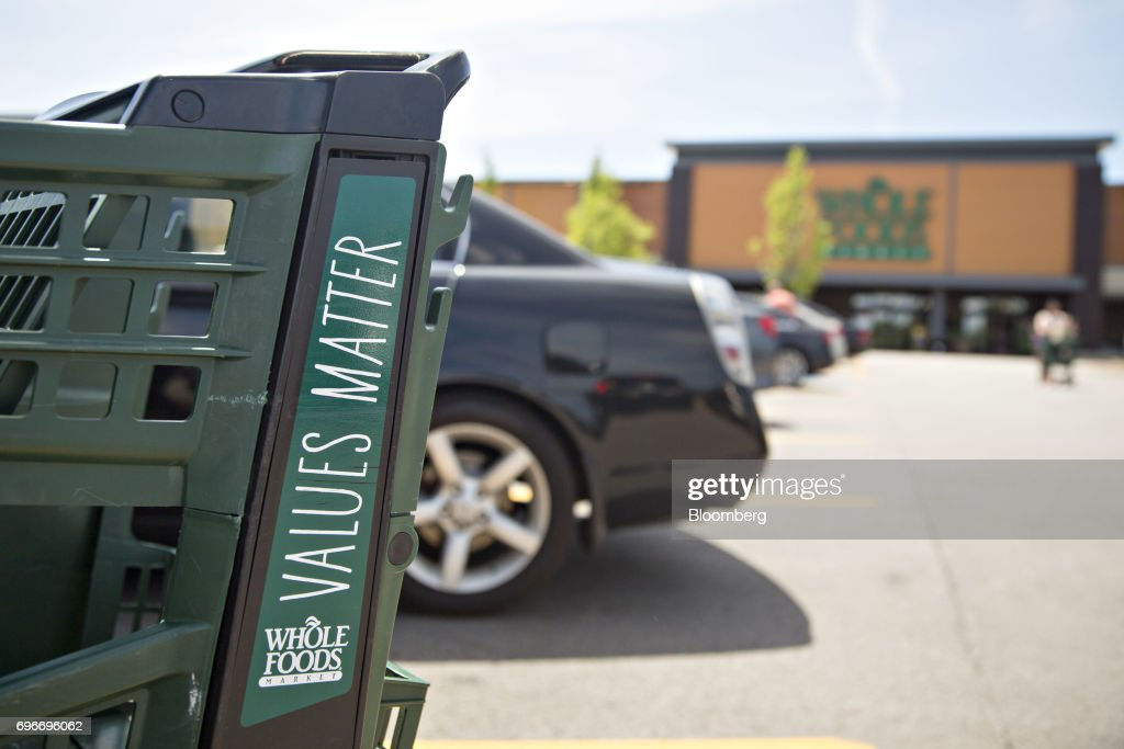A shopping cart sits outside a Whole Foods Market Inc. location in Willowbrook, Illinois, U.S., on Friday, June 16, 2017. Amazon.com Inc. will acquire Whole Foods Market Inc. for $13.7 billion, a bombshell of a deal that catapults the e-commerce giant into hundreds of physical stores and fulfills a long-held goal of selling more groceries. Photographer: Daniel Acker/Bloomberg via Getty Images