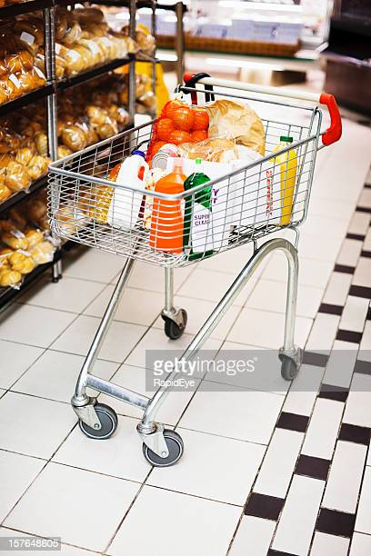Shopping cart with groceries next to supermarket bakery