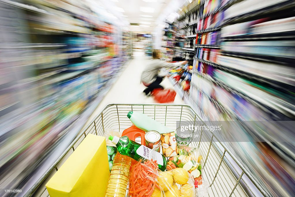 Shopping cart's speed creates rainbow motion blur in supermarket aisle : Foto de stock
