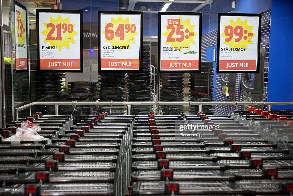 Shopping carts stand at a collection point below advertisements for special price offers inside an ICA supermarket store in Stockholm, Sweden, on Tuesday, Feb. 19, 2013. Hakon Invest AB, the minority owner of Sweden's largest food retailer ICA, agreed to take full control by acquiring partner Royal Ahold NV's 60 percent stake for 20 billion kronor ($3.1 billion). Photographer: Casper Hedberg/Bloomberg via Getty Images