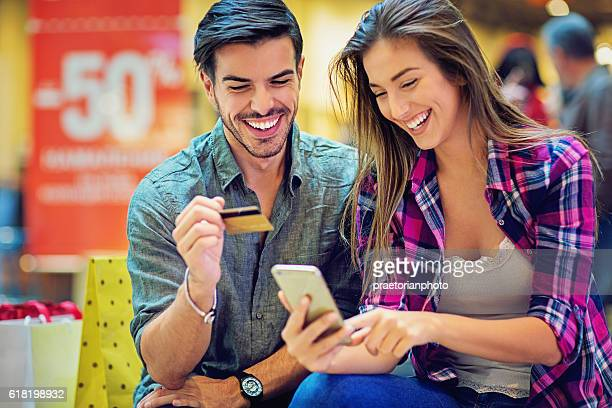 Shopping couple are buying online in the Mall