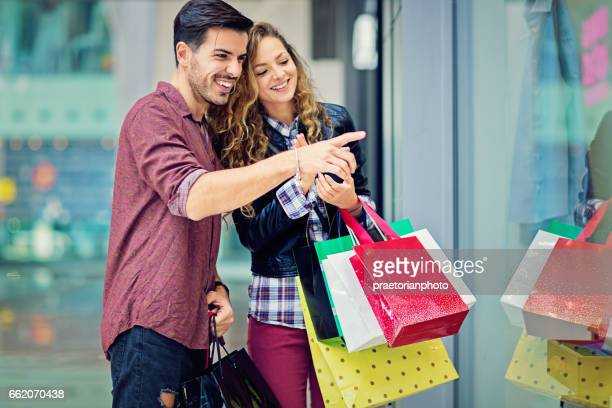 Shopping couple is  looking in the store window in the Mall