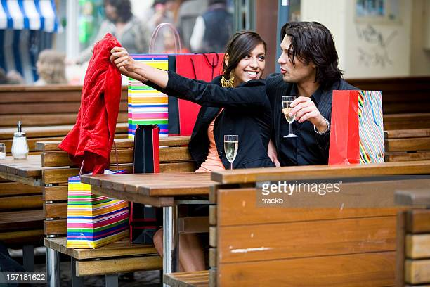 shopping: couple reviewing their shopping while having a drink