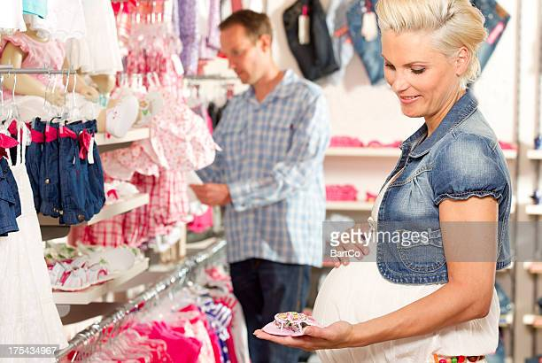 Shopping for baby clothes, holding shoes