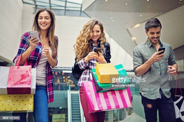 Shopping girls and man are texting in the Mall