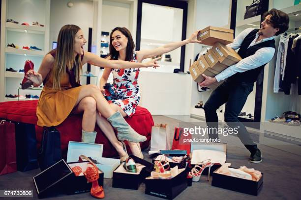Shopping girls are choosing shoes and asking from salesman for more