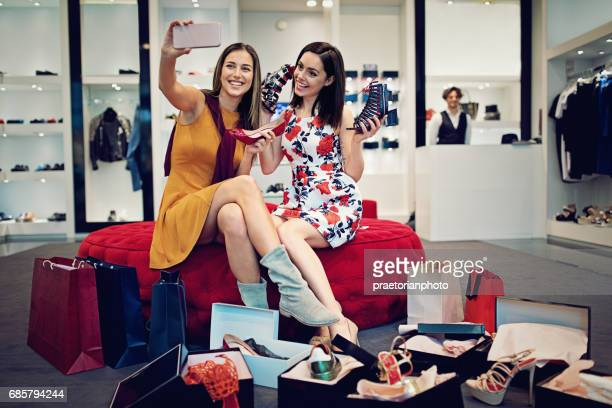 Shopping girls are choosing shoes and taking selfie with them