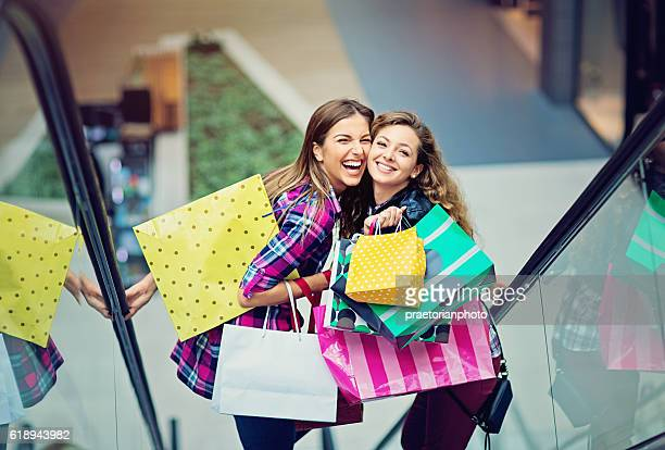 Shopping girls are laughing on the escalator in Mall