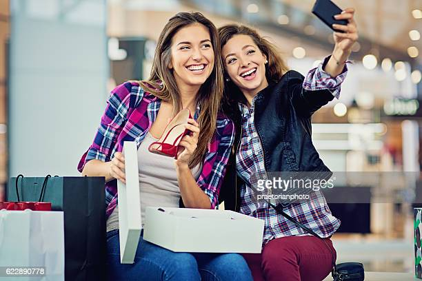 Shopping girls are looking their purchases in the Mall