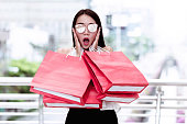 Portrait of young shopaholic woman with many red shopping bags, with surprise face as she see a sale sign. Taken outdoor in natural light.
