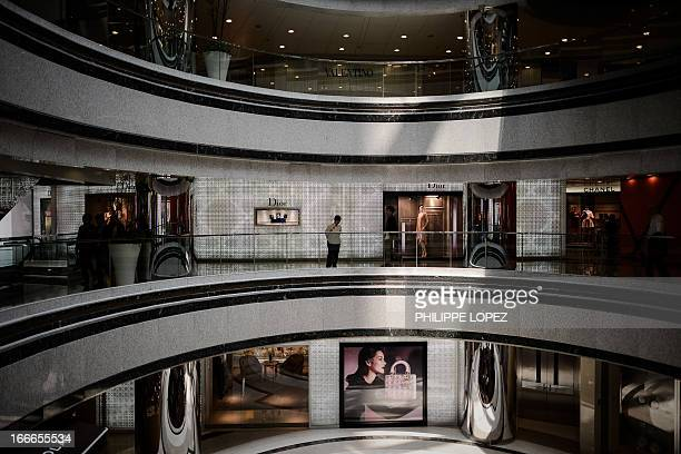 A shopping mall employee looks on next to luxury shops in Hong Kong on April 15 2013 The Asian financial hub is known for its courting of expensive...