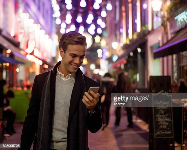 Shopping man texting on his phone