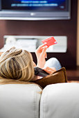 Young woman watching tv and using credit card