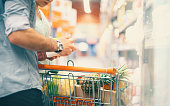 Two unrecognizable people shopping in supermarket. Choosing products and putting it in shopping cart. Rear view of casually dressed mid-aged couple.The guy is holding a product in white box and readin