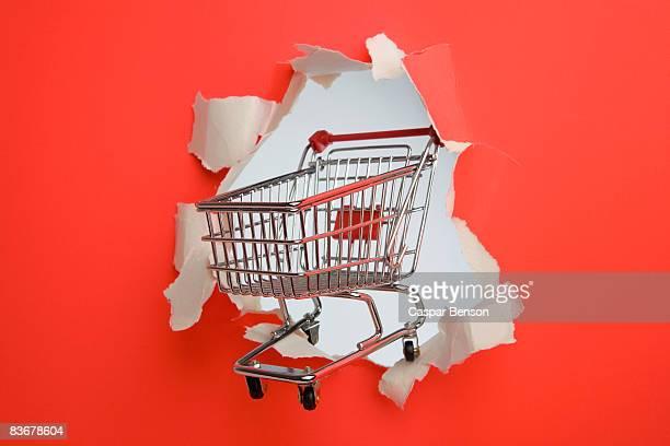 A shopping trolley breaking through a wall