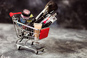 Shopping trolley full of make up and cosmetic goods on black concrete background. Black friday concept