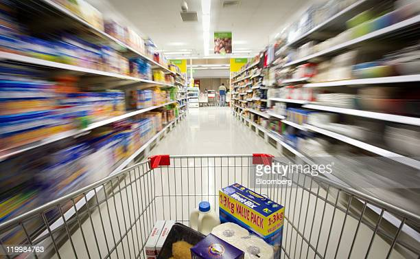 A shopping trolley is pushed through an aisle at a Wesfarmers Ltd Coles supermarket in Sydney Australia on Thursday July 28 2011 Wesfarmers Ltd...