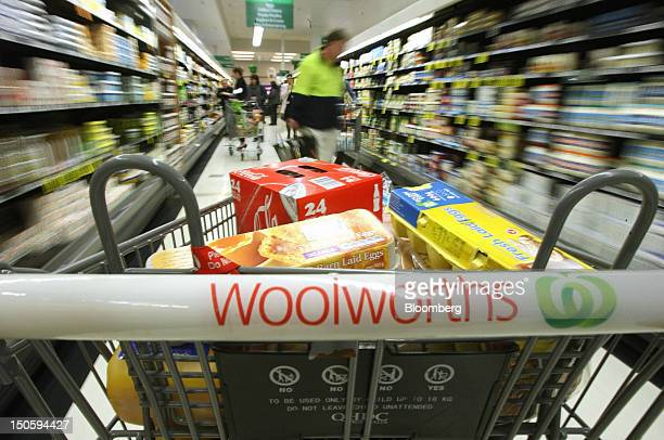 A shopping trolley is pushed through an aisle at a Woolworths Ltd supermarket in Perth Australia on Wednesday Aug 22 2012 Woolworths Australia's...