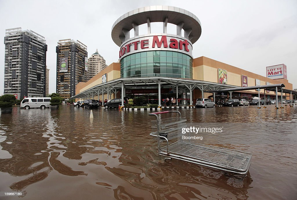A shopping trolley stands in floodwaters in front of a Lotte Shopping Co. Lotte Mart supermarket in Jakarta, Indonesia, on Friday, Jan. 18, 2013. Indonesia declared a state of emergency in Jakarta as flooding brought traffic to a standstill in the city of 9.6 million people and swamped the offices of President Susilo Bambang Yudhoyono. Photographer: Dimas Ardian/Bloomberg via Getty Images