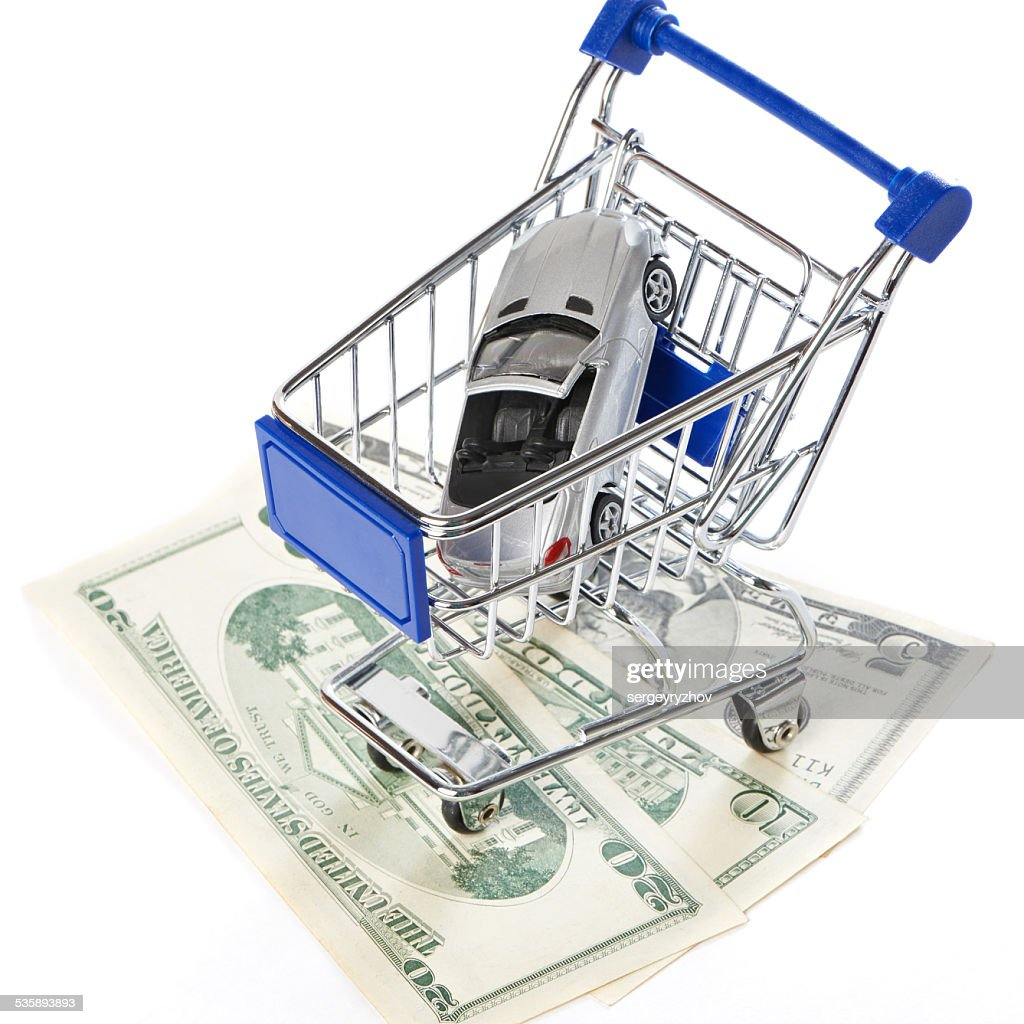Shopping trolley with money and toy car : Stockfoto