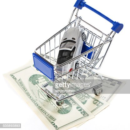 Shopping trolley with money and toy car : Stock Photo