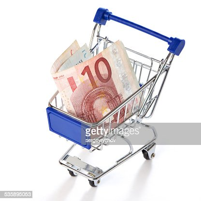 Shopping trolley with money isolated : Stock Photo