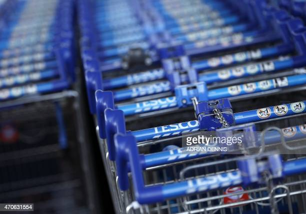 Shopping trolleys are pictured outside a Tesco supermarket in Sunbury west of London on April 22 2015 Britain's biggest retailer supermarket group...