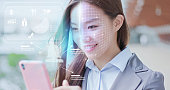 A business woman is shopping on smart phone with scanning facial recognition.