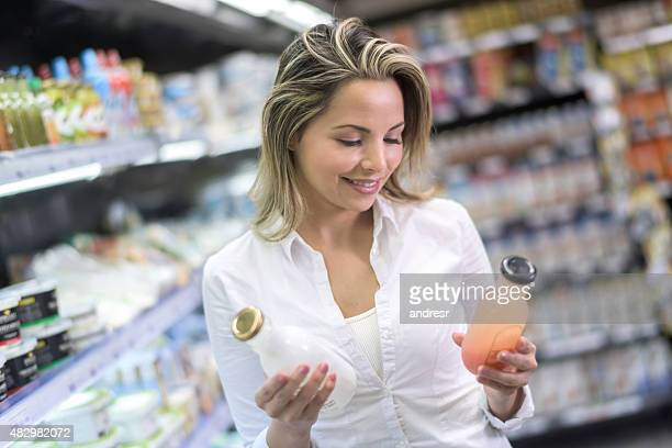 Shopping woman comparing products at the supermarket