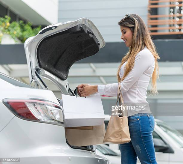 Shopping woman putting bags in the car