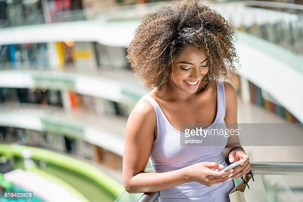 Shopping woman texting on her cell phone
