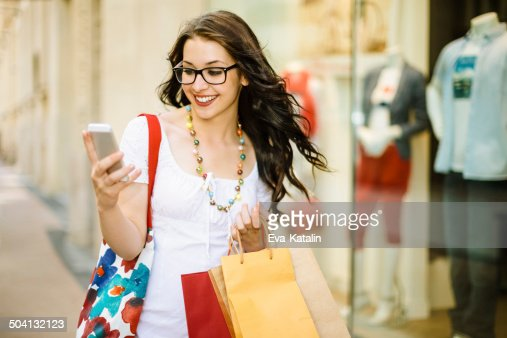 Shopping woman wearing glasses is texting downtown