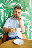 Young man in cafe using phone and drinking coffee