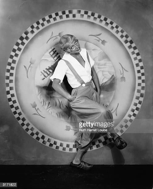 Short haired blonde wearing Dutch trousers and clogs film star Joan Crawford dances in front of a drawing of a windmill plate edged with tulips